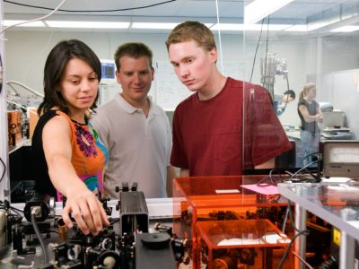 Visiting graduate student, discusses geometrics of the high-powered laser in the Keck Laboratory with Colorado State University electrical and computer engineering graduate student and undergraduate student.