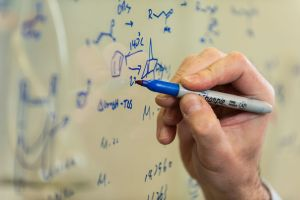A chemistry researcher writes chemical formulas on the glass of a hood.