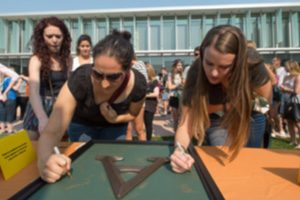 Photo of students signing an Aggie plaque at Transfer Orientation.