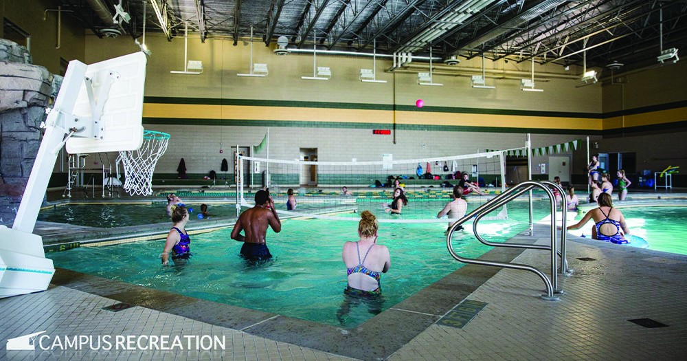 Students play volleyball in the pool.