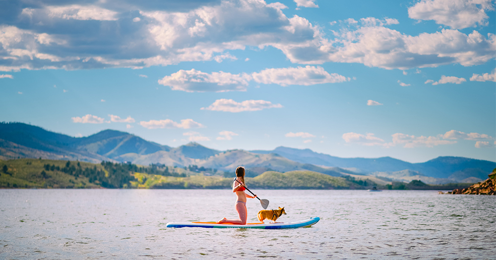 A student paddle boards on the Horsetooth Reservoir
