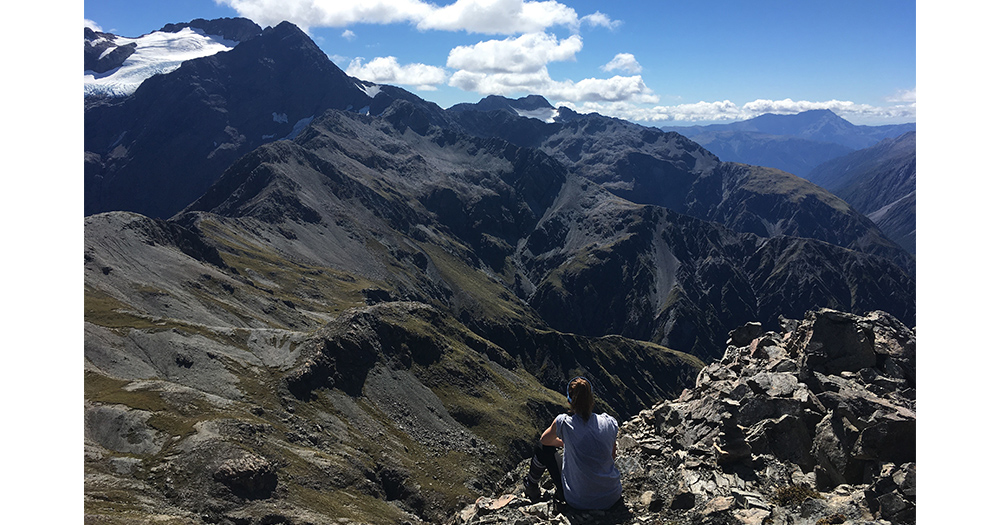 Rebecca hikes to a beautiful summit in New Zealand.