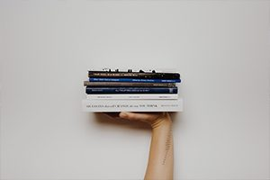 Hand holding up stack of books