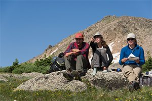 three students listen to an outdoor lecture in the mountains.