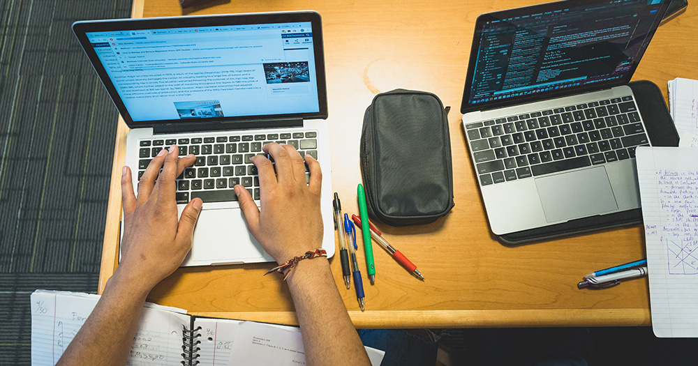 Two laptops are open on a desk; one set of hands types on one laptop. There are pens and papers around.