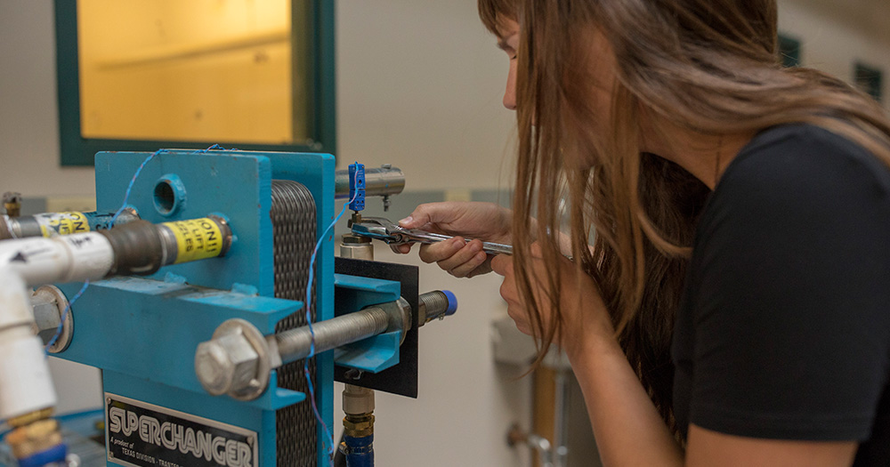 A mechanical engineering student works with technology on a class project.