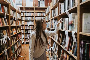 student looking at books in a library aisle