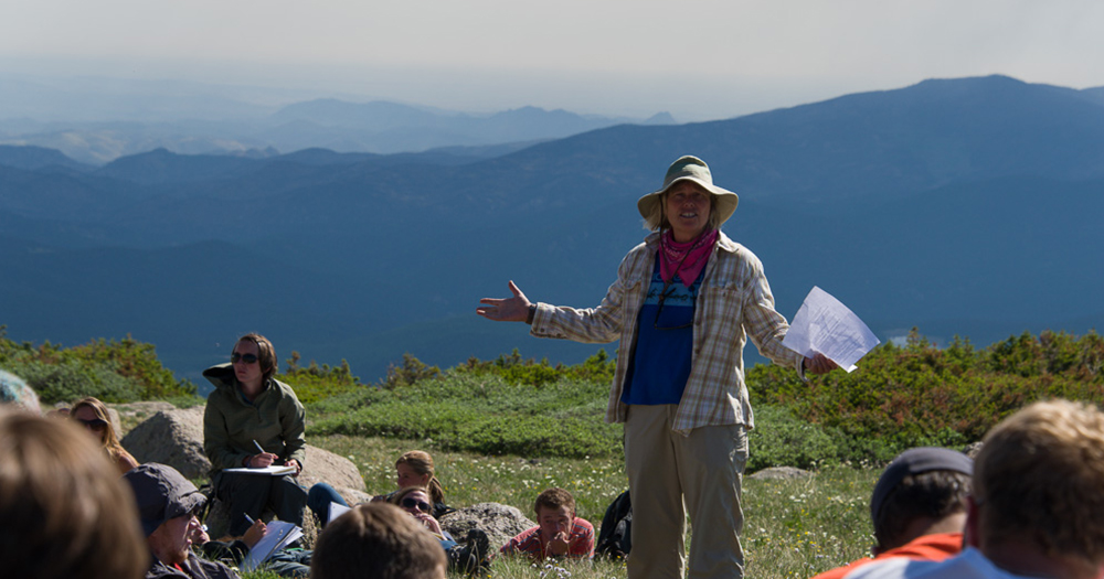 a teacher instructs to a class on the top of a mountain