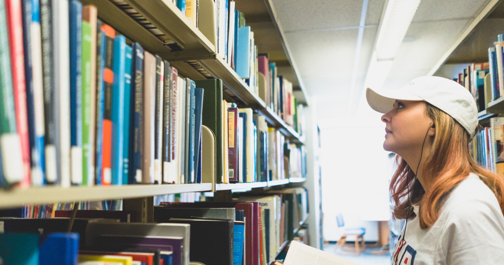 A student looks at books on a library shelf.