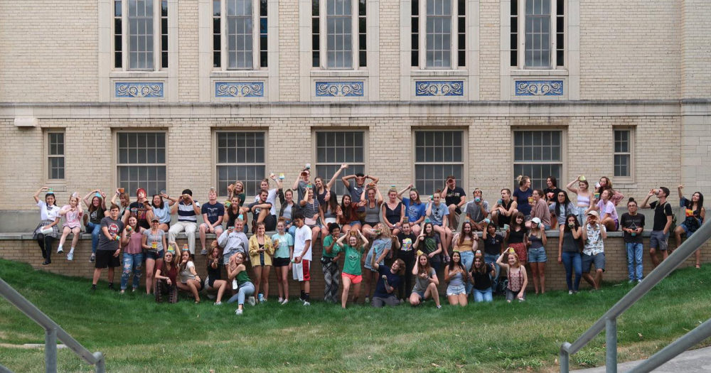 A large group of students pose in a lawn outside