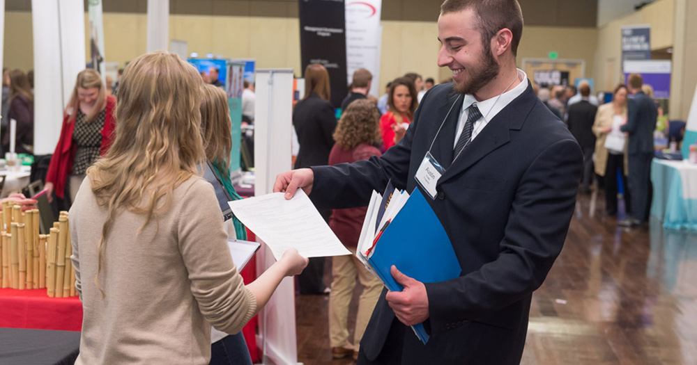 a student passes out a resume at a job fair