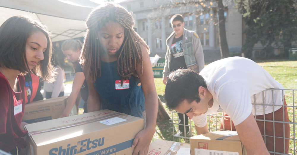 Students helping weigh boxes of food