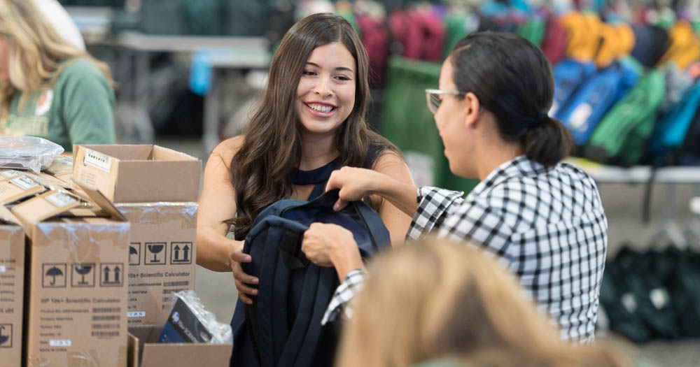 Student helping fill backpacks with supplies