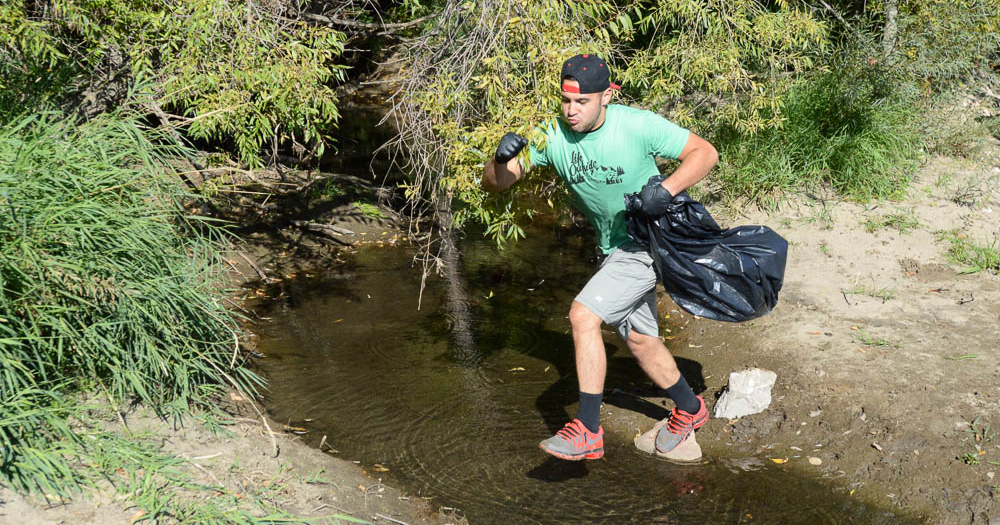 Student hopping creek to pick up trash