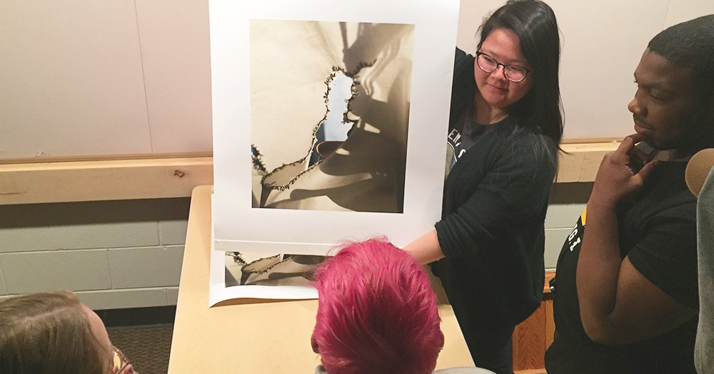 A photography student showcases her work to peers