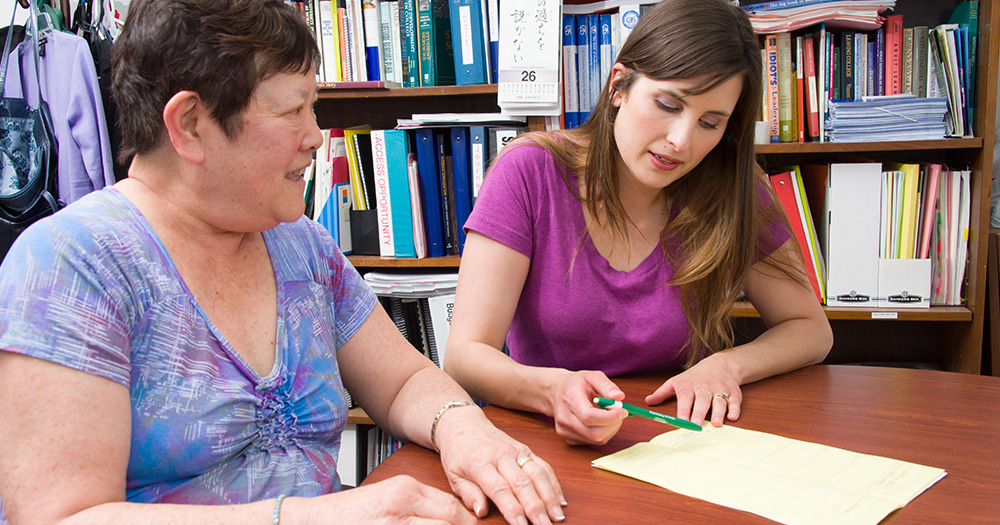 Social work student meeting with a community member in office