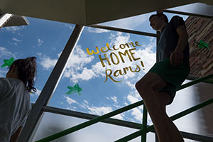 "People walk down stairs next to a window with ""Welcome Home Rams"" painted on it."