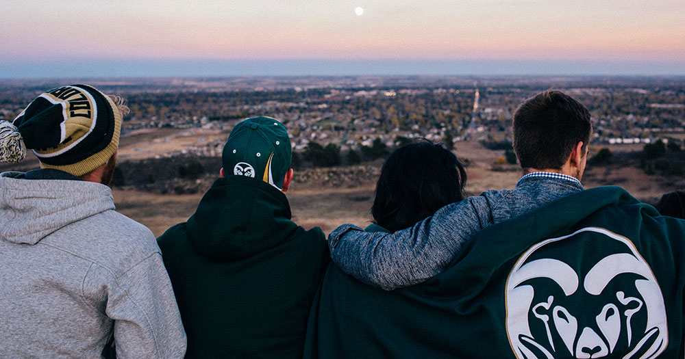 Four students wearing CSU gear sit closely on a ridgeline and enjoy a sunset and a view of Fort Collins.