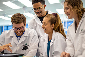 students do lab work in white lab coats