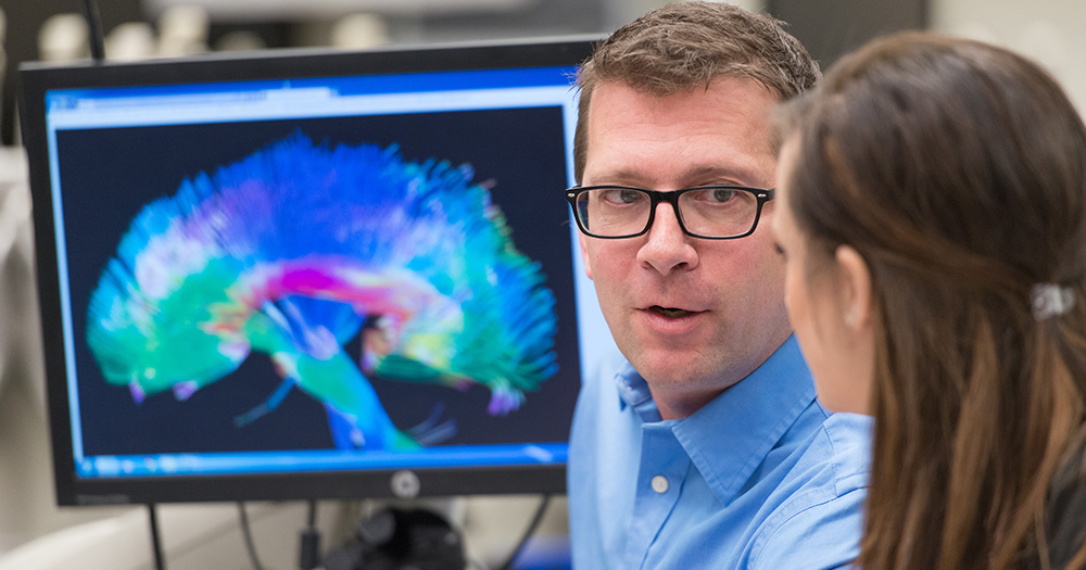 a neuroscience student works with a professor near a brain scanner