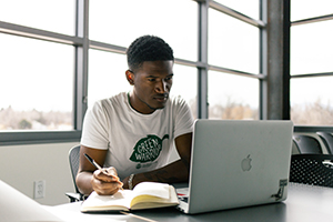 A student takes notes while reading from a laptop in a room with large open windows looking out onto campus.