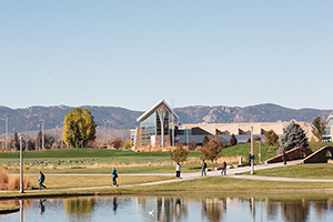 A small lagoon, green space and the CSU Rec Center are seen with mountain foothills in the background.