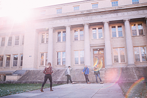 Four students gather in front of the Administration Building at Colorado State as the sun shines down onto campus.