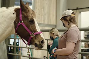 Student stands with horse in stall