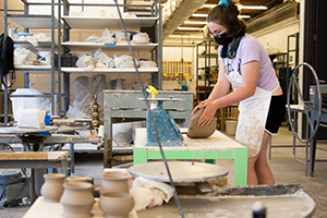 A colorado state pottery student works in the studio